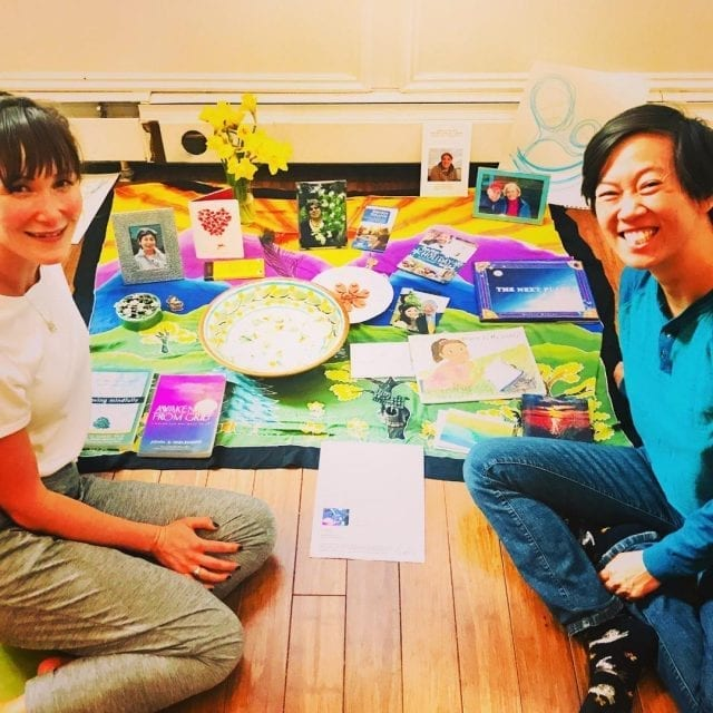 Amy Hyun Swart and Amber Field sitting in front of a grief altar